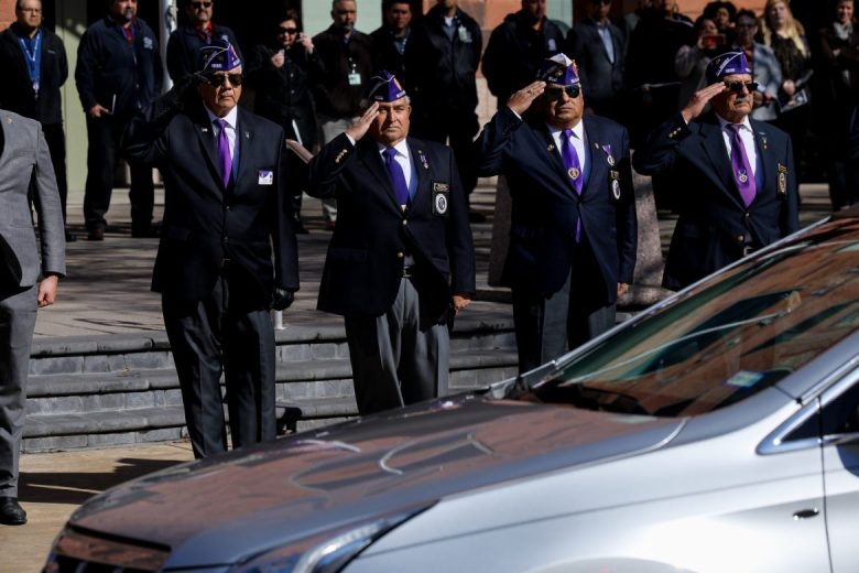 The Military Order of the Purple Heart salute as the hearse carrying Paul Elizondo passes by Paul Elizondo Tower.