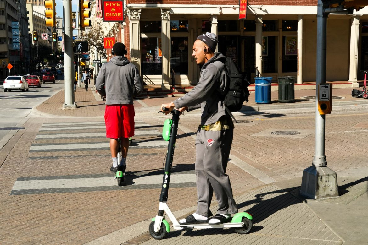 A scooter operatior crosses Alamo Street at Commerce.