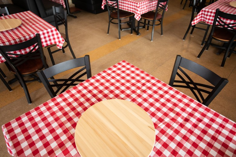Red and white checkered tablecloths line all the tables and booths throughout the restaurant.