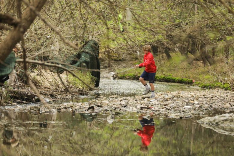 Oliver Gwin, 12, crosses the creek bed as he works his way downstream collecting trash and recyclables.