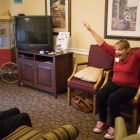 Activity assistant Winifred Carlock (right) leads residents in stretches to begin their day.