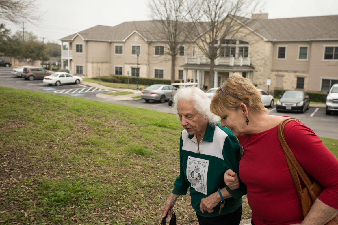 Activity assistant Winifred Carlock (right) walks from building 2 to building 1 with resident Joan Harris.