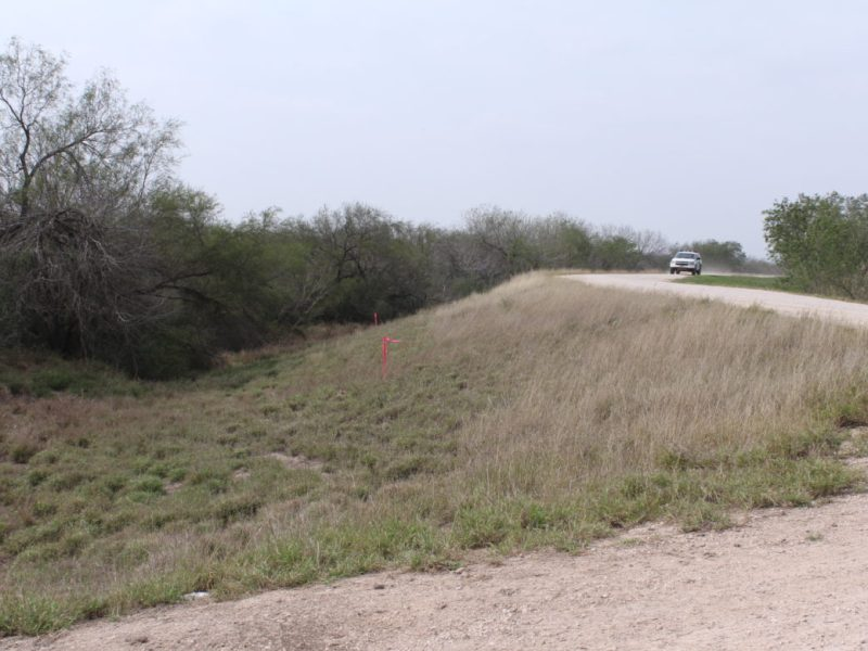 Stakes with pink flags mark a possible border wall boundary near a levee, where a Border Patrol vehicle cruises by.