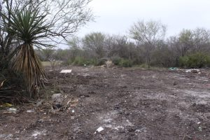 A torn-up patch of ground scattered with trash on the Cox tract.