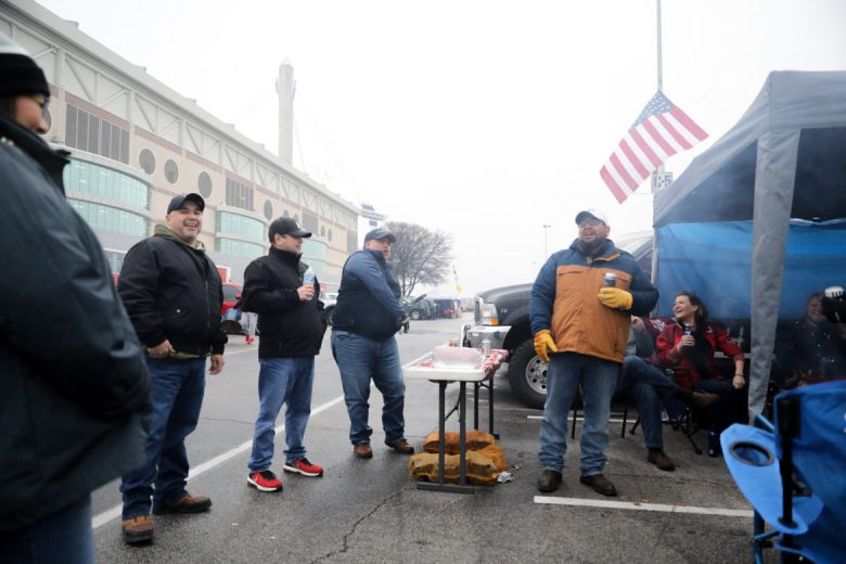 Commanders fans tailgate before the game begins in the cold temperatures outside the Alamodome.