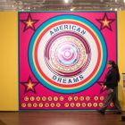 A security guard walks past the entryway of the American Dreams: Classic Cars and Postwar Paintings exhibition.