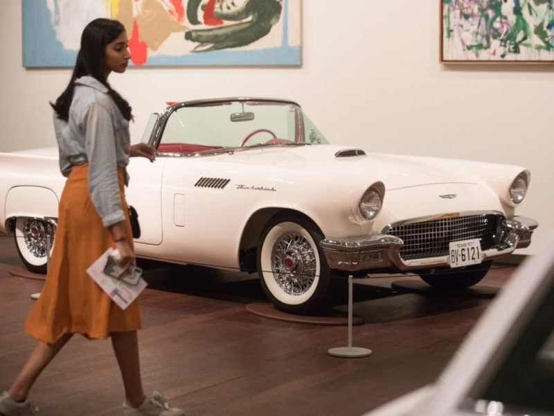 A young woman walks through the American Dreams: Classic Cars and Postwar Paintings exhibition.