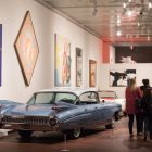 People walk through the American Dreams: Classic Cars and Postwar Paintings exhibition.