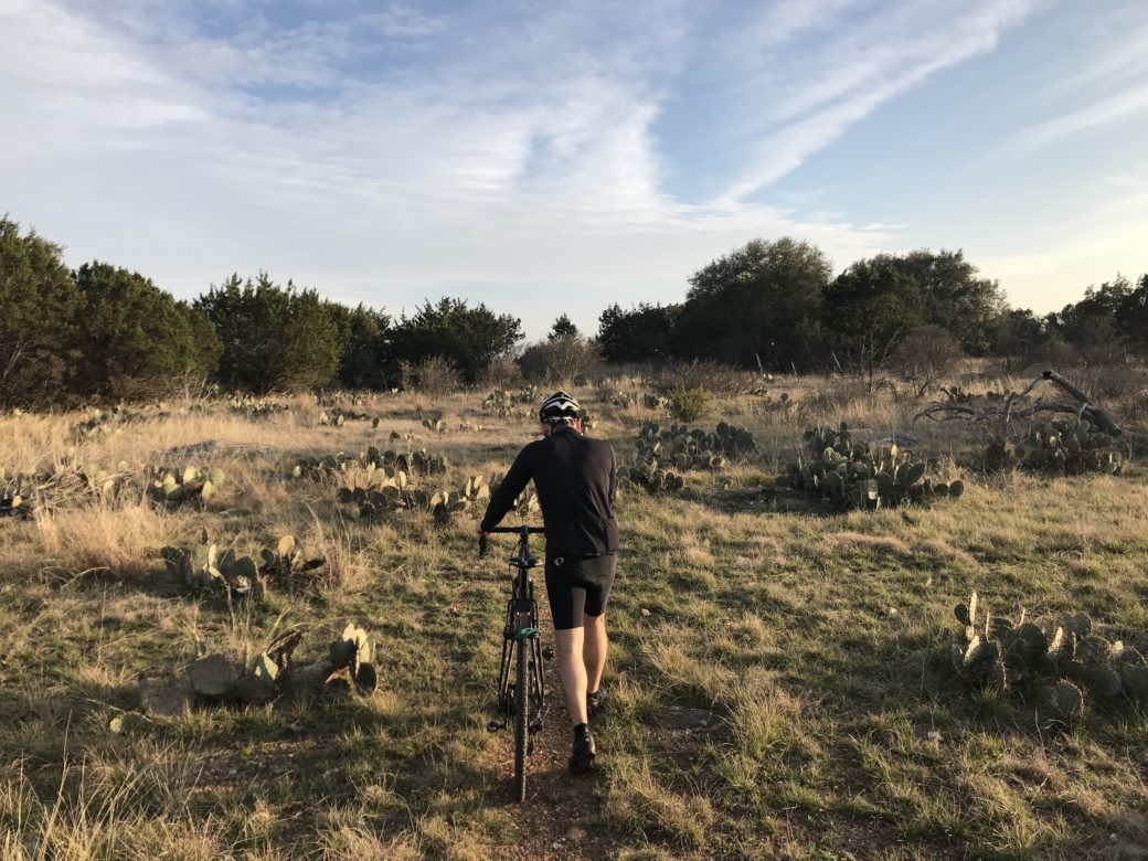 Max O'Roark pushes his bike past patches of prickly pear at Colorado Bend State Park.