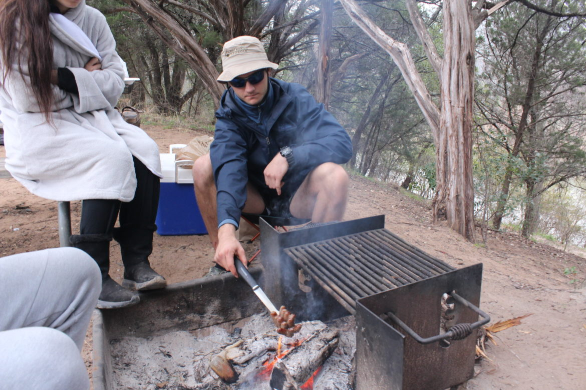 Kevin Currie roasts breakfast sausage on a campfire.