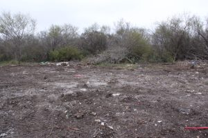 A moonscape of bare dirt, tire tracks, trash, and bonfire ash on a part of the Cox tract at Pearsall Park in early February.