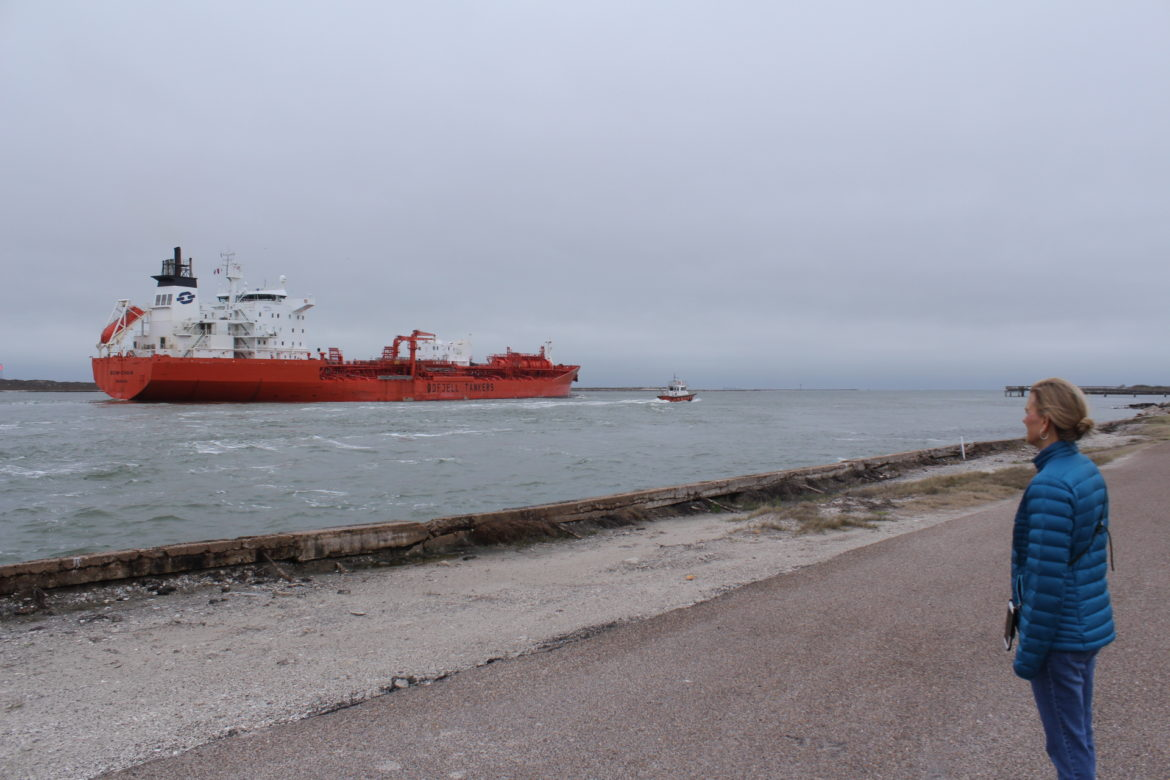 Tammy King watches as a chemical tanker passes through the ship channel just off Port Aransas.