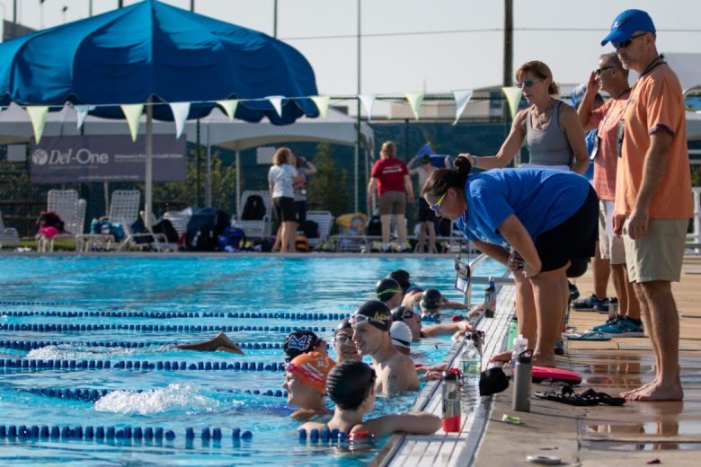 Special Olympics swimming coach Elizabeth Waugh leans down to talk to her swimmers during practice.
