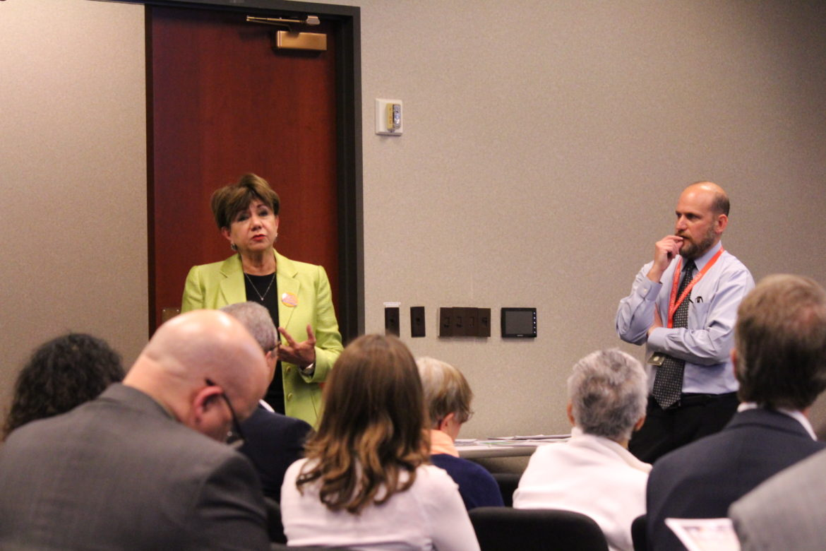 San Antonio Hispanic Chamber of Commerce CEO Diane Sánchez, left, speaks to a crowd about the City's climate plan, while City Chief Sustainability Officer Doug Melnick watches.