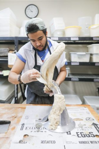 Kenny Freeman scrapes large pieces of fresh dough off of an industrial sized dough hook letting nothing go to waste.