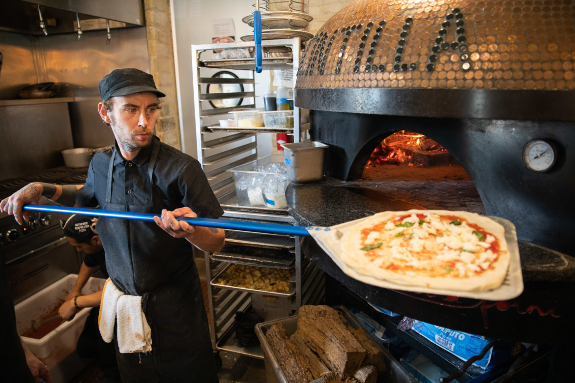 Lance Schopieray brings a pizza into the wood burning oven.