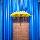 A yellow umbrella with blue streamers acting as rain is designed for social media platforms like Instagram.