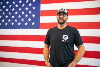 Dustin Ray, owner of Palm 91 stands in front of a large backdrop of an American Flag at his new business.