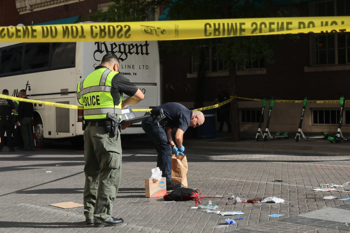 Police use a trash bag to clear a scene where a pedestrian was struck and killed by a bus in downtown San Antonio.