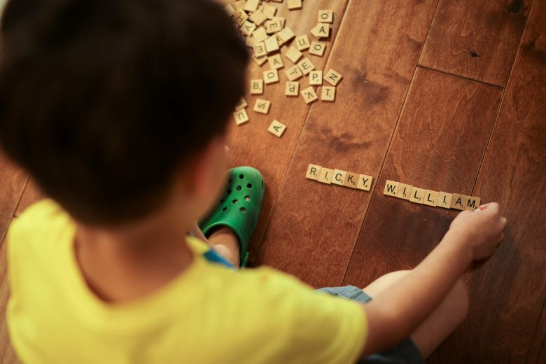 Ricky spells his name with Scrabble pieces on the floor at Lion's Field Senior Center.