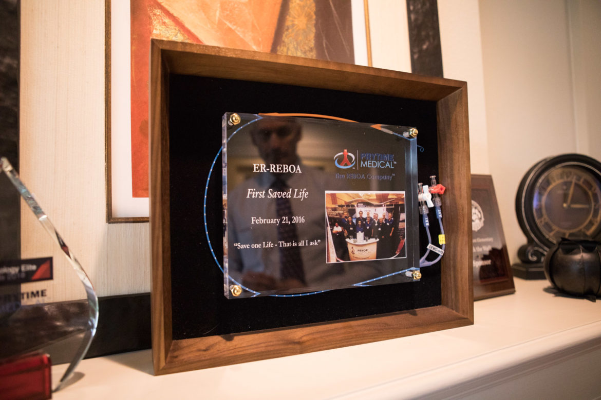 David Spencer is reflected in the glass of the ER-REBOA First Saved Life award.