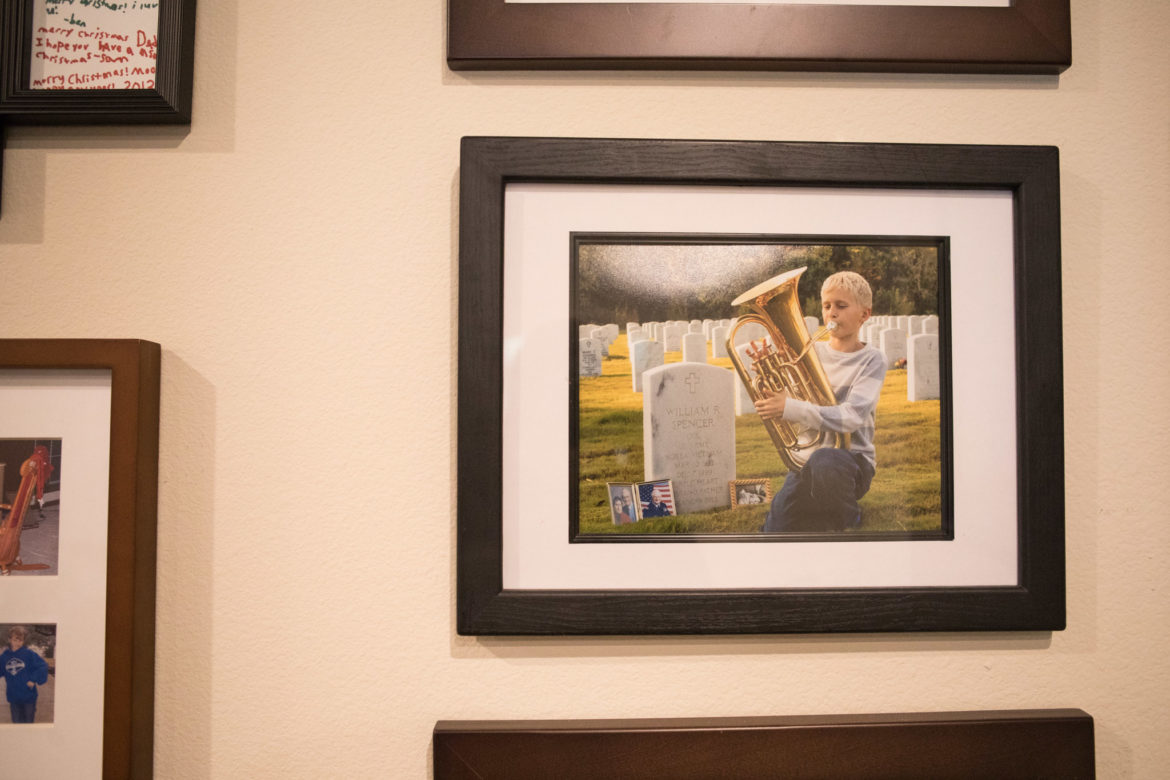 A photograph in David Spencer's office of his son playing in front of his father's grave.
