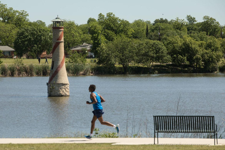 A man runs past the lighthouse at Woodlawn Lake Park.