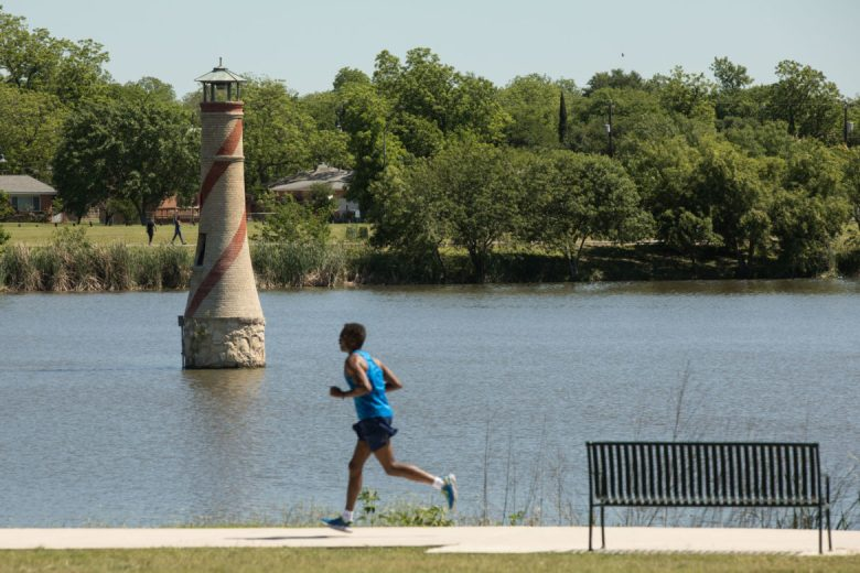 A man runs past the lighthouse at Woodlawn Lake Park.