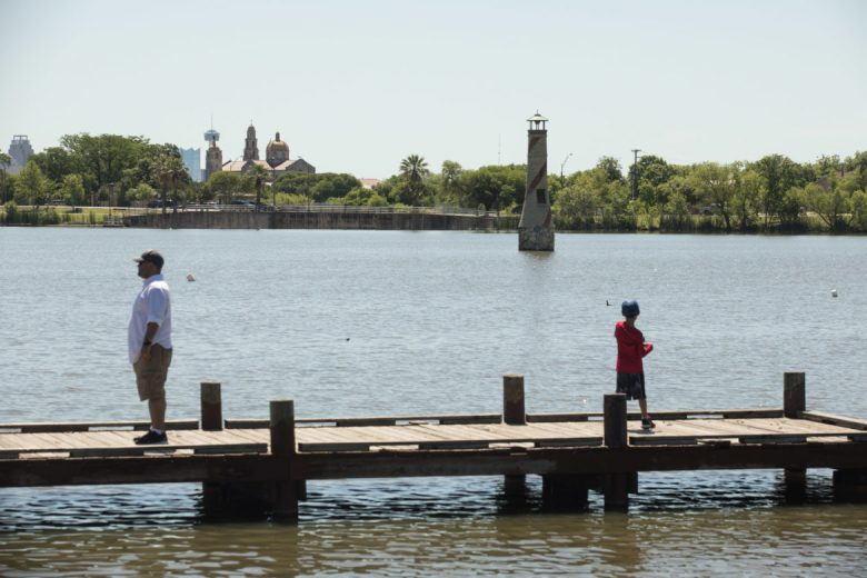 A young boy fishes with a view of the lighthouse and downtown at Woodlawn Lake Park.