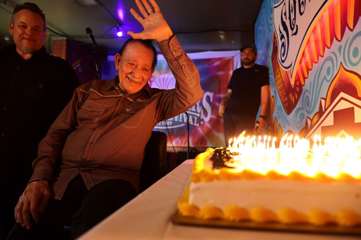 Legendary musician Flaco Jiménez waves to the audience moments before blowing out the candles on his 80th birthday cake at Squeezebox.