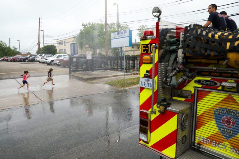 Children run through water shot from a fire truck as it falls from above.