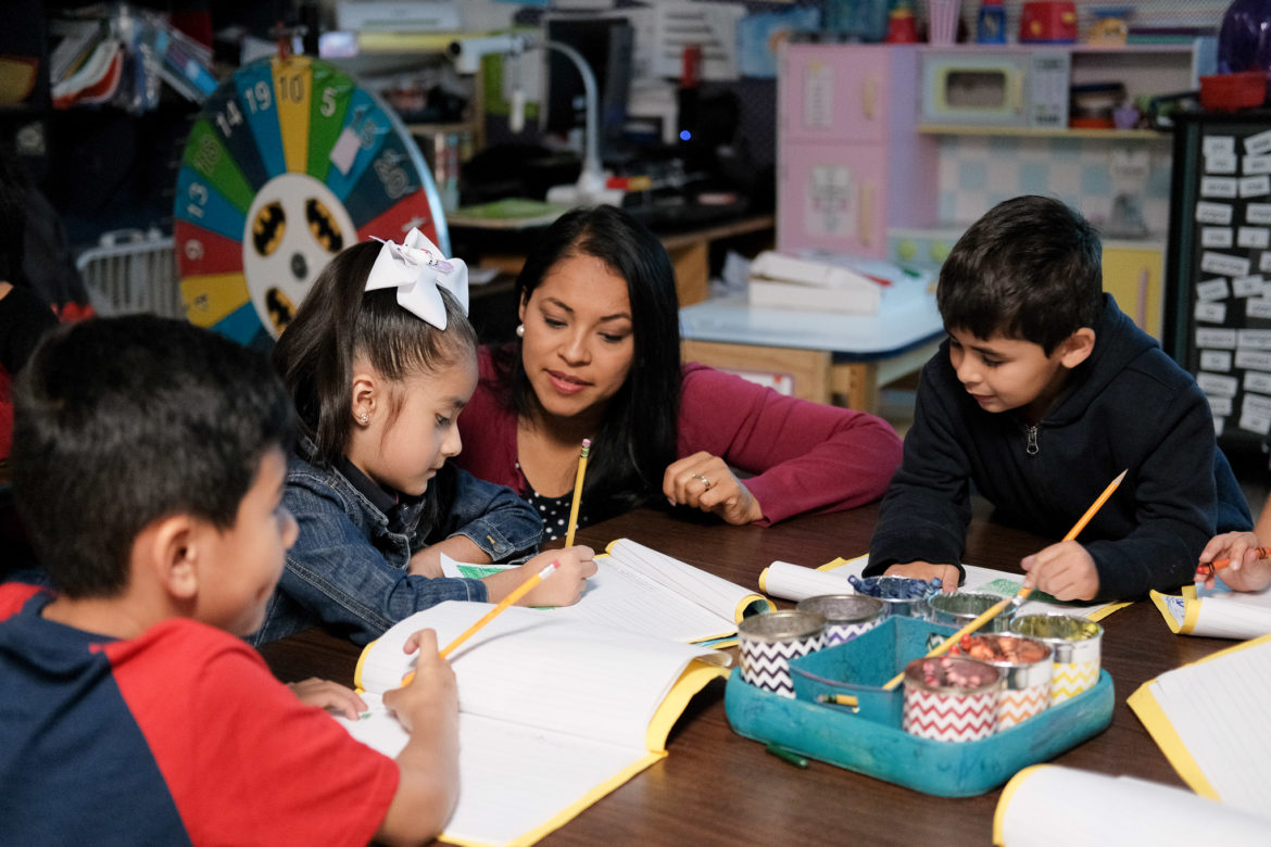 Teacher Miriam Hernandez works with a student during an assignment.