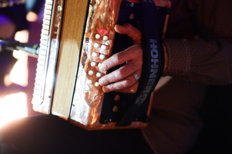 Flaco Jiménez' left hand in its familiar place on the Stradella bass system on the left side of his accordion.