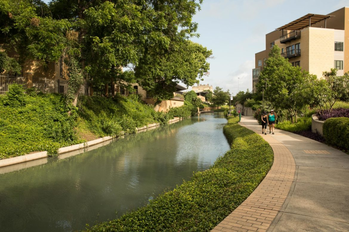 Pedestrians walk along the Museum Reach across the river from the San Antonio Art Museum.