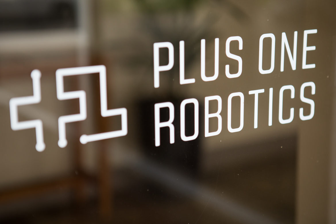 A sticker identifies Plus One Robotics on the entry to the building.