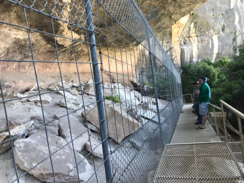 Visitors to Panther Cave observe the rock art from outside a cage that prevents intruders from damaging the paintings left behind thousands of years ago.