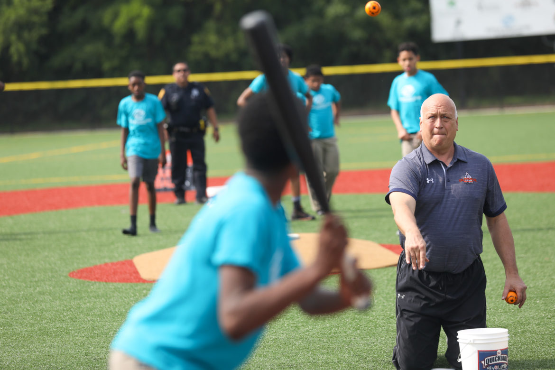 Cal Ripken Jr. throws balls to members of the Boys & Girls Club Eastside Branch on their new baseball field.