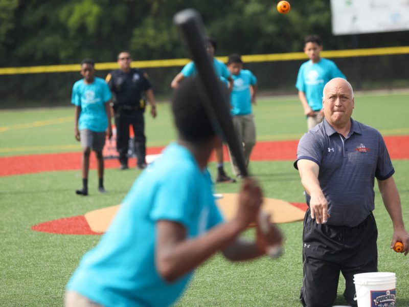 Cal Ripken Jr. throws balls to members of the Boys & Girls Club Eastside Branch on their new baseball field.