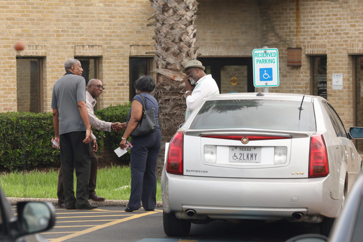 District 2 candidate Keith Toney shakes hands with voters as they head into the polls at the Claude Black Community Center.