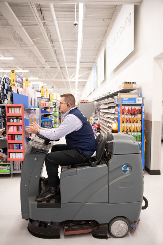 Wal-Mart Store Manager Jason Justice drives the robotic floor cleaner to its destination.