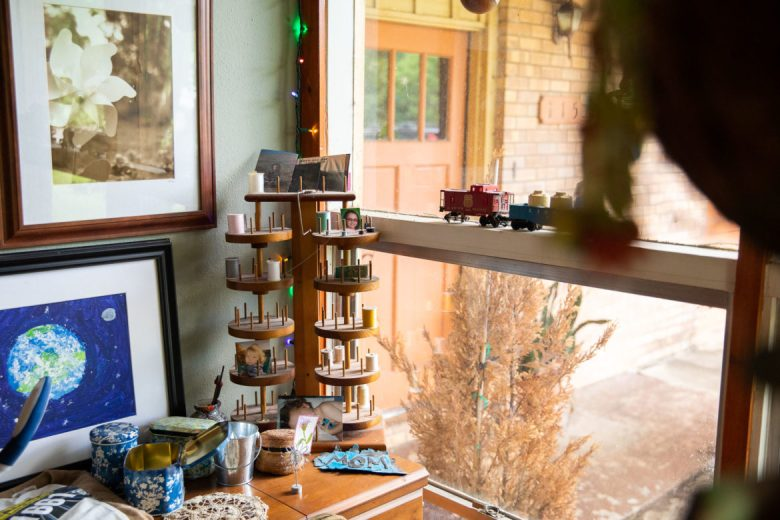 A rotating spool rack sits at the corner of Amy's house filled with thread and family photographs.