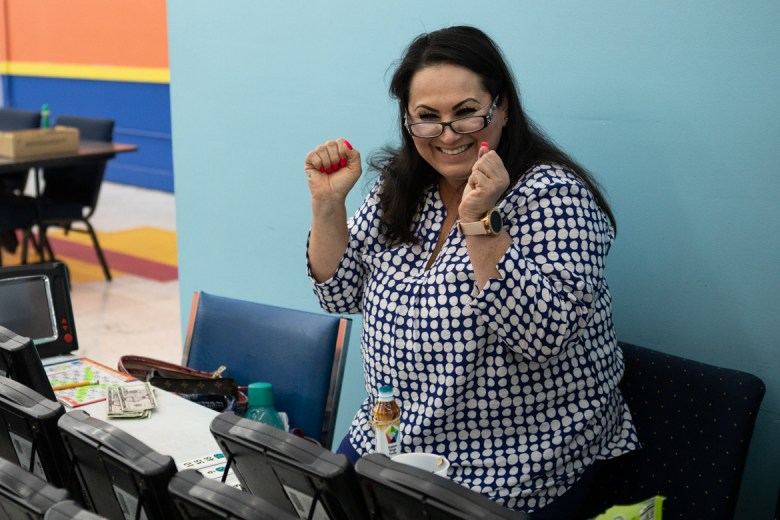 Judy De Leon waves her fists in the air after she wins a round of bingo.