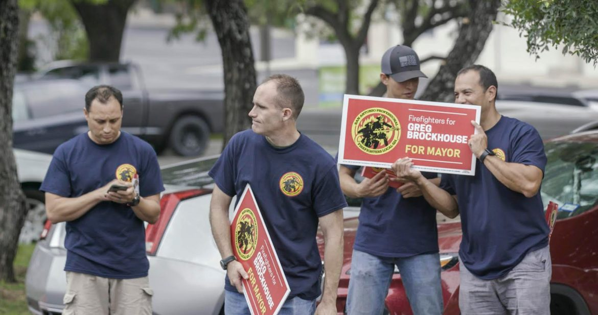 Firefighters hold signs in support of Greg Brockhouse at Cody Library earlier in the week.