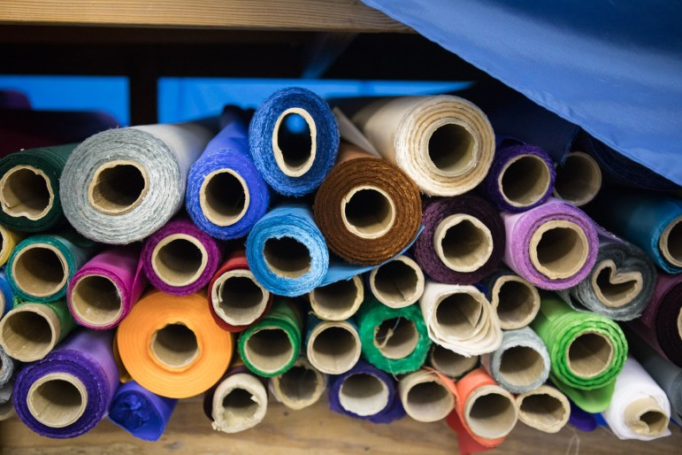 Rolls of nylon material are stored underneath the tables in the sewing area.