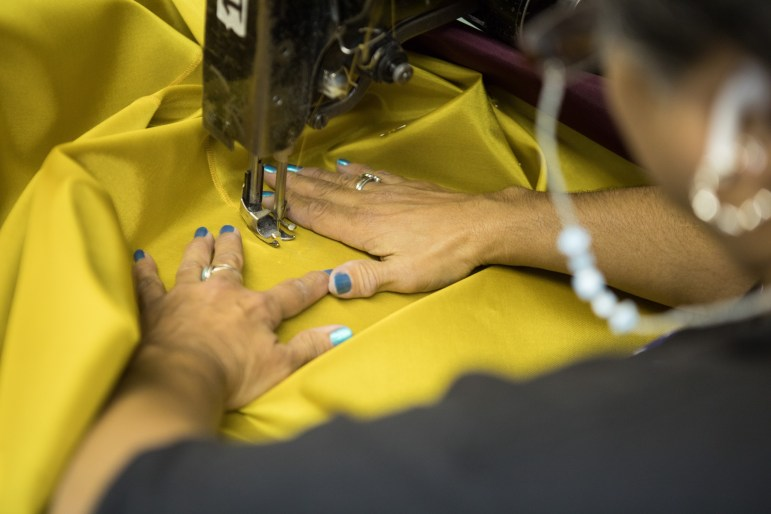 Lucy Rodriguez, lead seamstress, sews a flag.