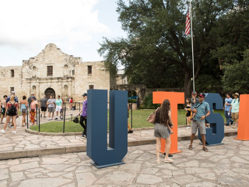 Passers-by take photos with the large UTSA letters in front the Alamo.