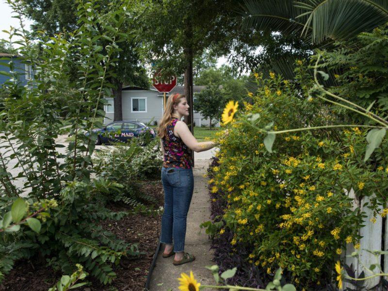 Taylor Watson admires a neighbor's garden in Mahncke Park.