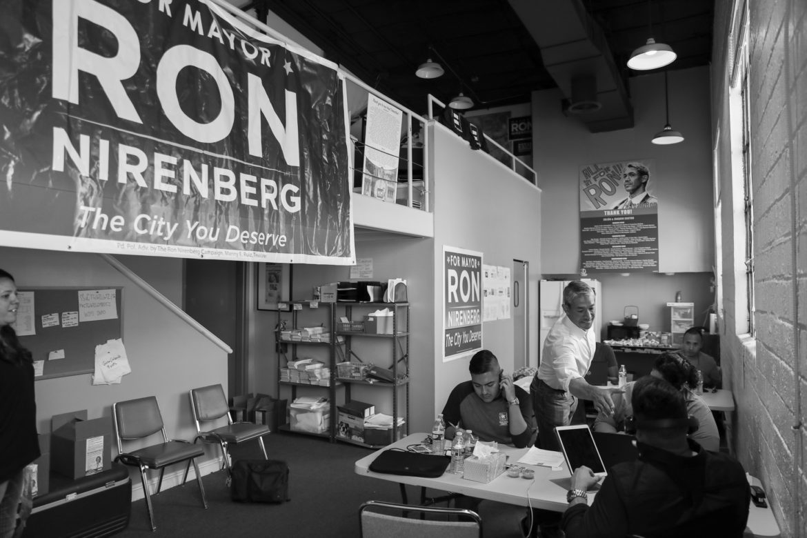 Mayor Ron Nirenberg shakes hands with campaign volunteers at his campaign office.