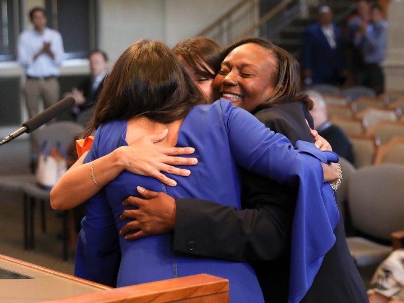 Councilwomen Melissa Cabello Havrda (D6), Jada Andrews-Sullivan (D2), and Adriana Rocha Garcia (D4) hug each other after they are sworn in as City Councilmembers.