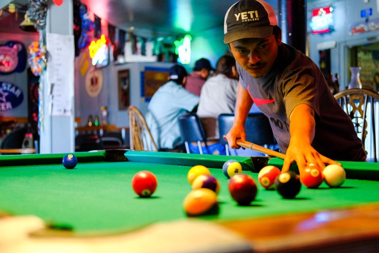 Samuel Rodriguez just moved to San Antonio from North Carolina and plays a game of pool with his father, Guillermo.